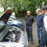Michael Fries (l.) und Dominik Nagel (r.) zeigen Thomas Grewe, welche Besonderheiten sich unter der Motorhaube des Peugeot 5008 verbergen.